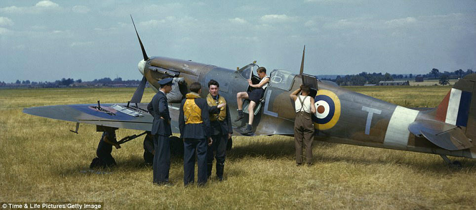 Pilots chatting, as the aircrew work on their Spitfire